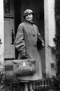 A woman in a long overcoat and leather satchel stands outside a building.