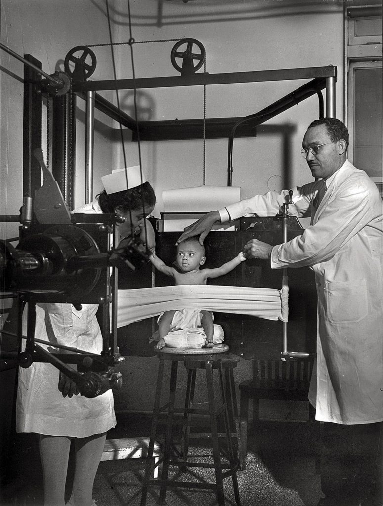 Old photo of a Black nurse and doctor taking an x-ray of a baby with a huge old machine