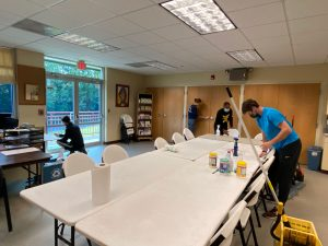 people cleaning a large conference room