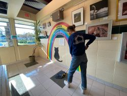 person mopping the floor in front of a rainbow mural
