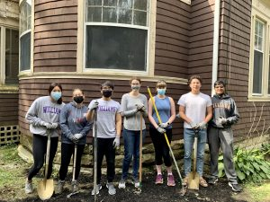 people posing with shovels and rakes