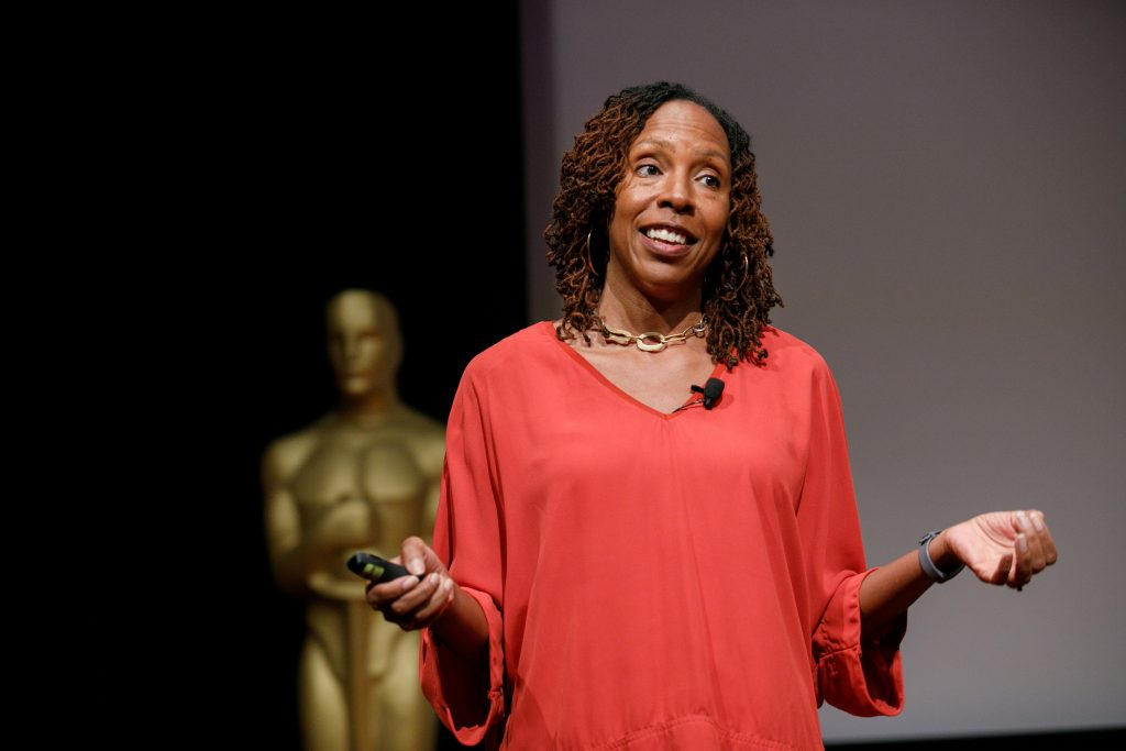 Woman in a red shirt speaking to an audience in front of a golden Oscar Award statue